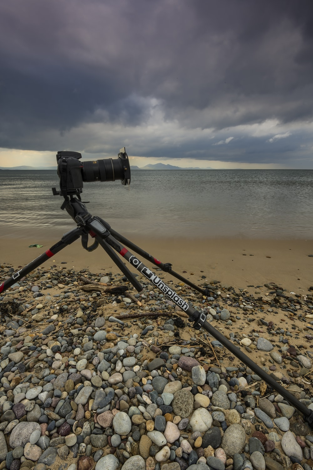 black camera on black tripod on brown sand near body of water during daytime