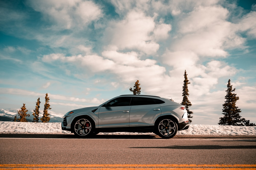 blue coupe on gray asphalt road under white clouds and blue sky during daytime