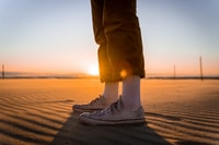person in blue denim jeans and white sneakers standing on brown sand during daytime