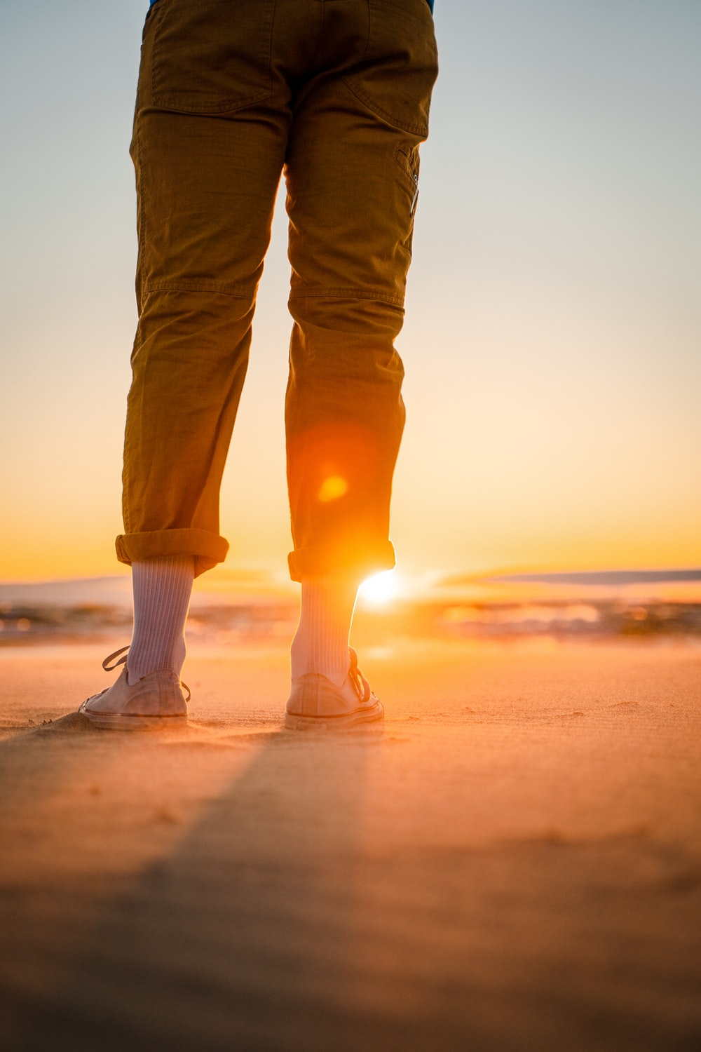 person in brown pants and white socks standing on beach during sunset