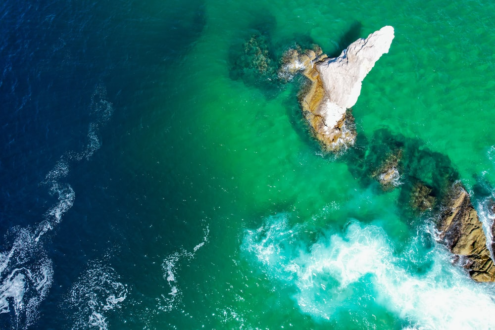 aerial view of white and brown rock formation on body of water during daytime