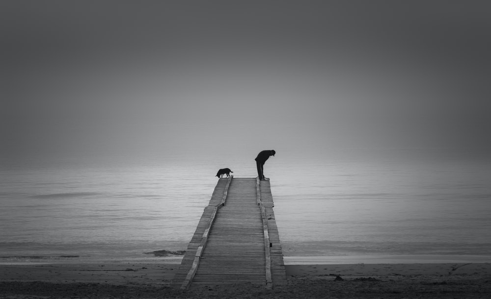 person walking on wooden dock in grayscale photography