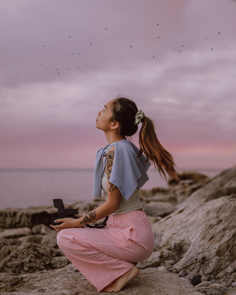 woman in white shirt and pink pants sitting on rock during daytime
