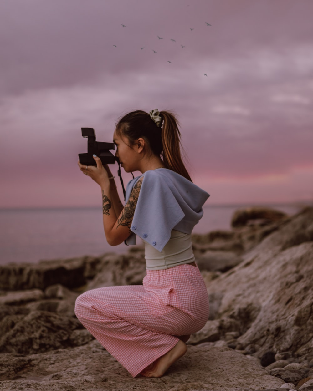 woman in white shirt and pink pants holding black smartphone