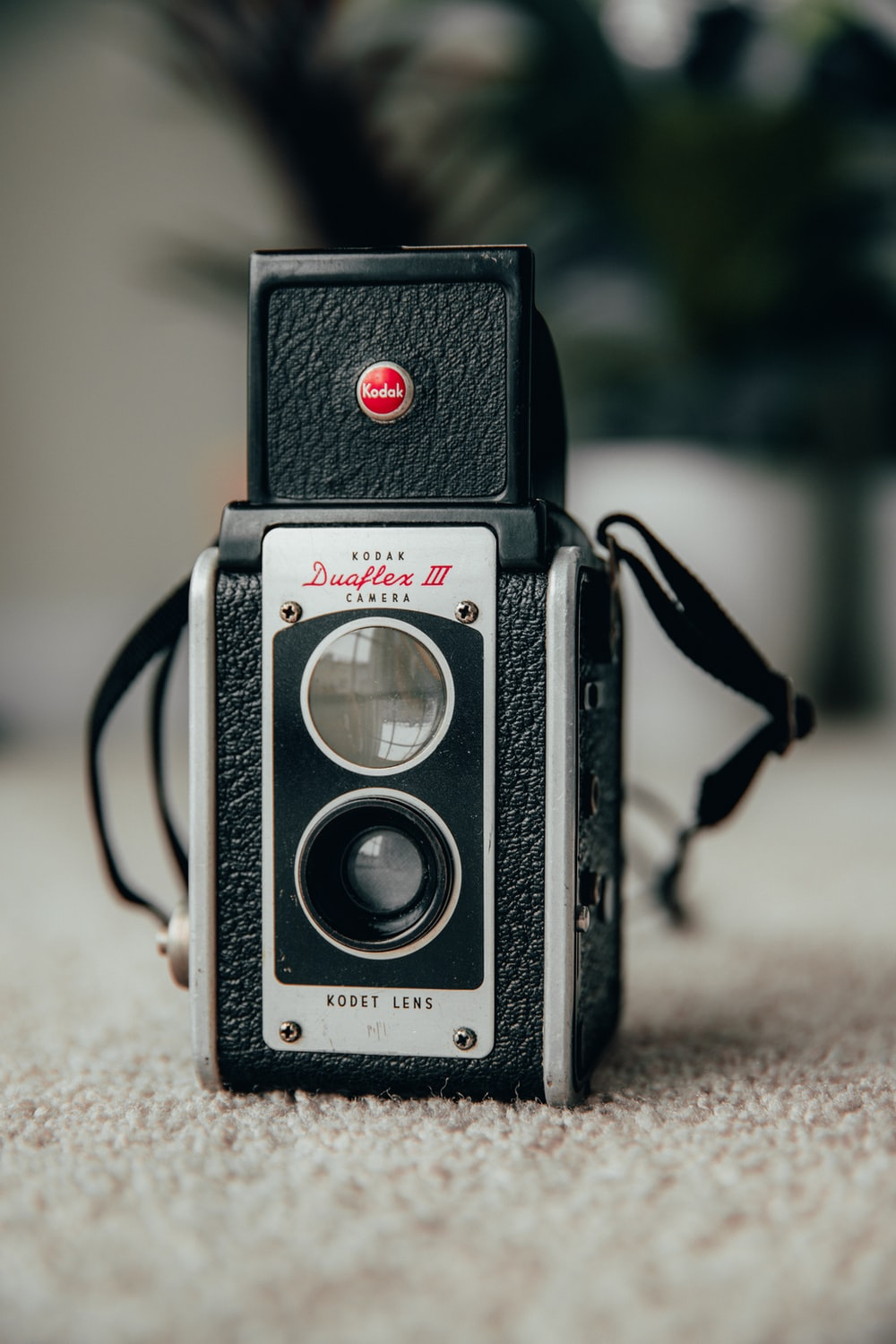 black and silver pentax camera on brown textile