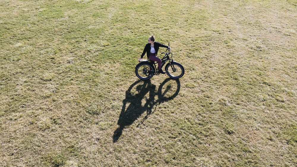 girl in pink jacket riding on bicycle on green grass field during daytime