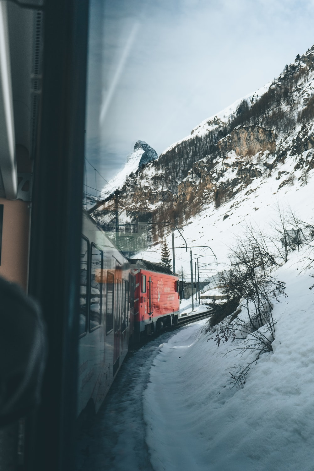 red train on rail tracks near snow covered mountain during daytime