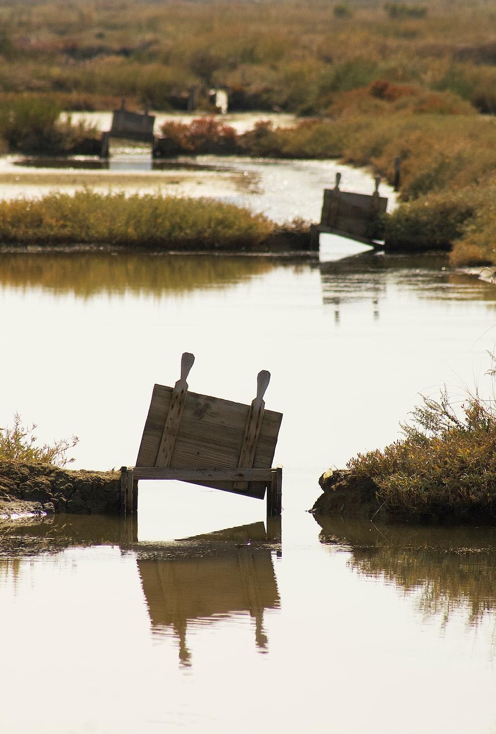 brown wooden bench on lake dock during daytime