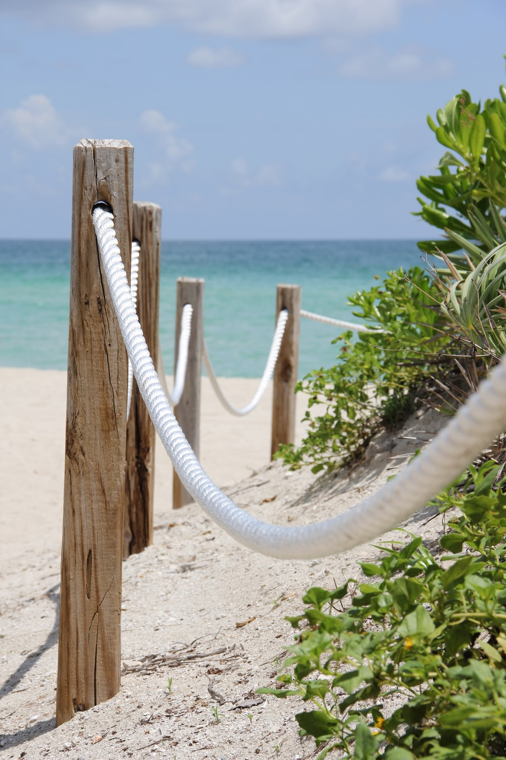 white rope tied on brown wooden post near sea during daytime