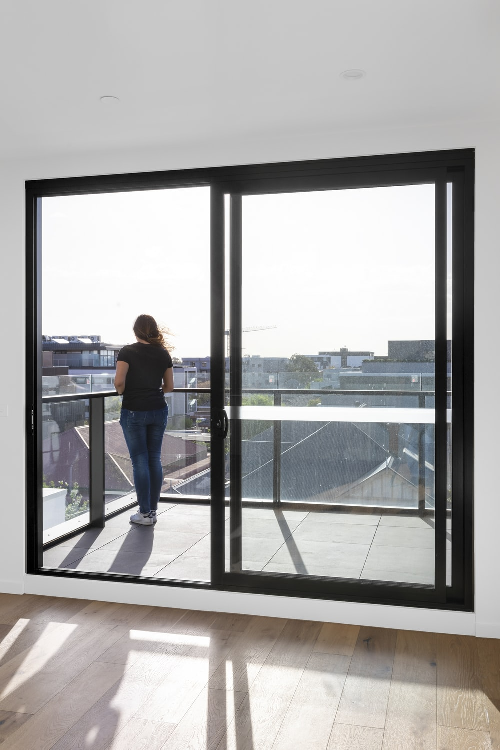 woman in blue denim jeans standing near glass window during daytime