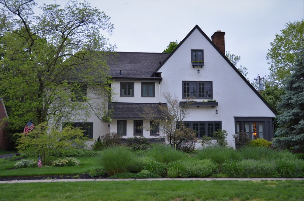 white and gray house near green grass field during daytime