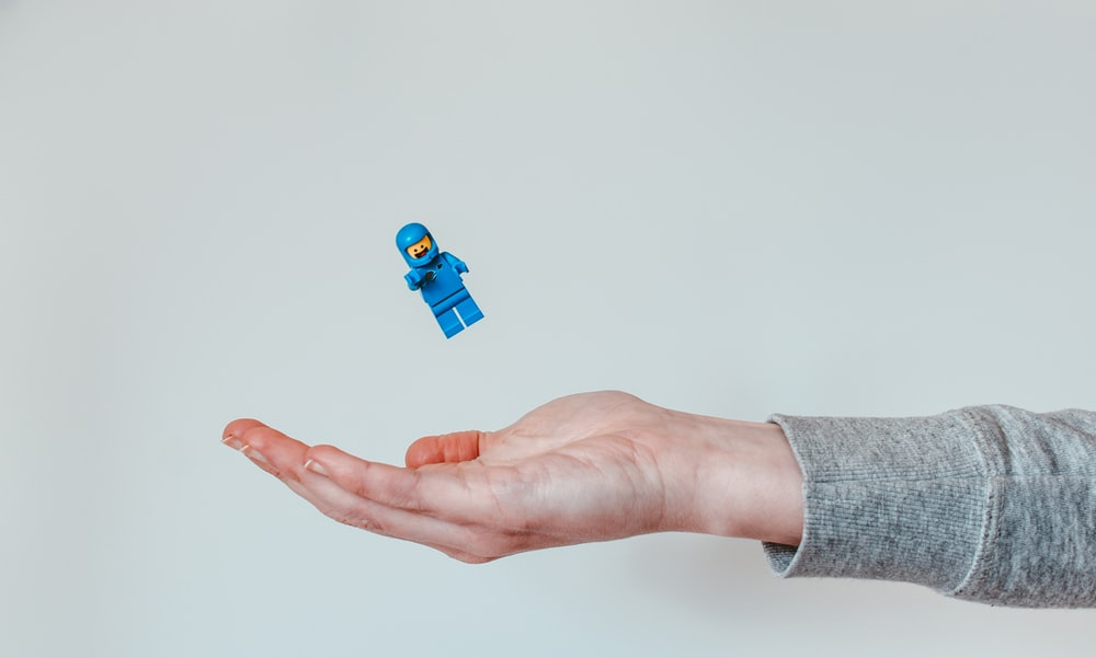 person holding blue lego toy