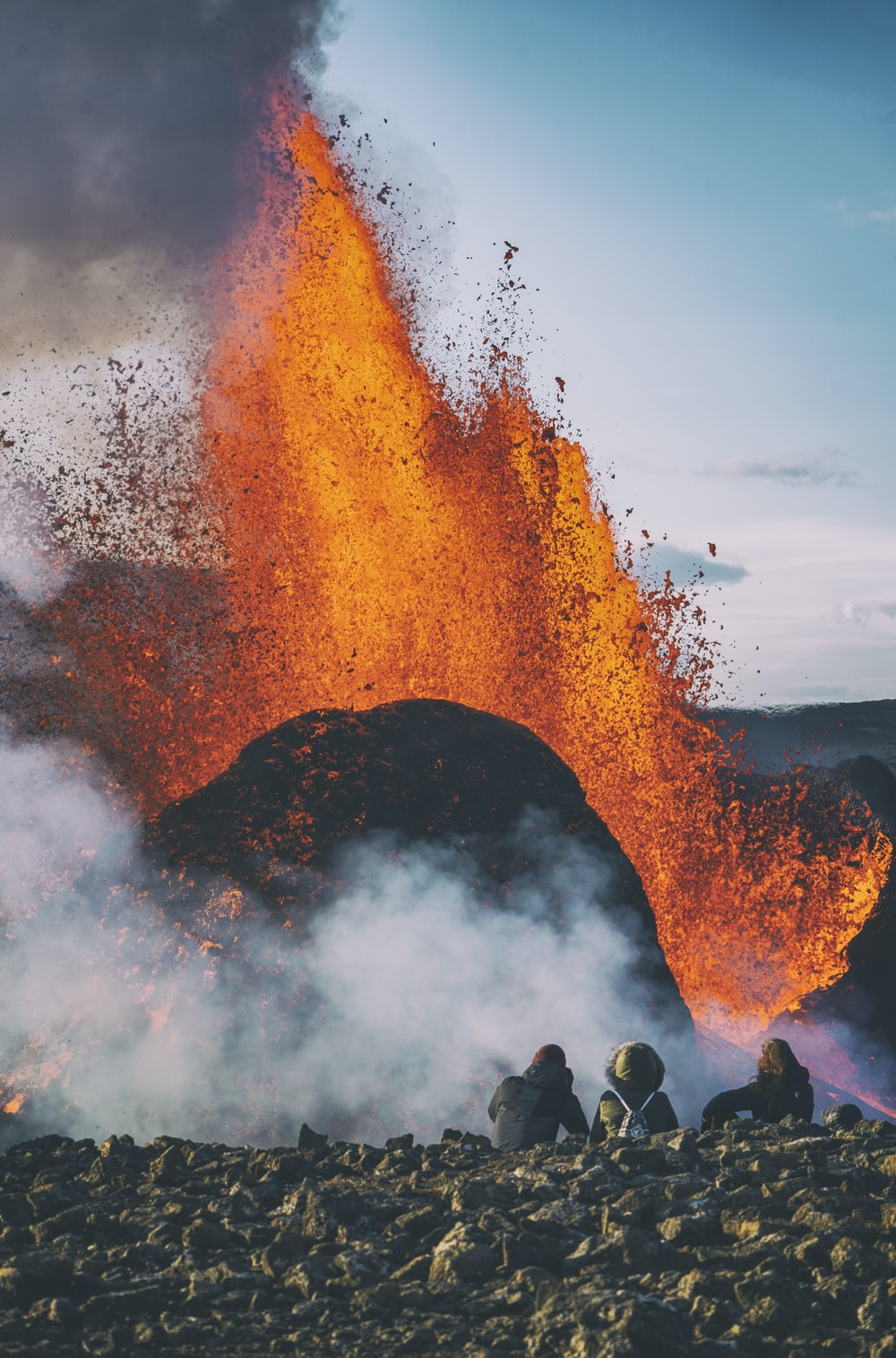 people standing on rock formation with fire during daytime