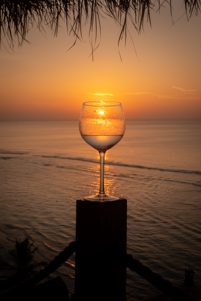 clear wine glass on brown wooden table during sunset