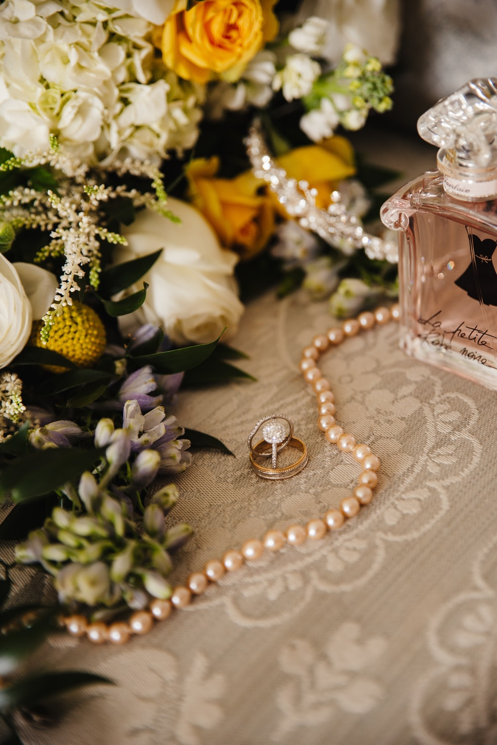 gold and silver beaded necklace beside perfume bottle