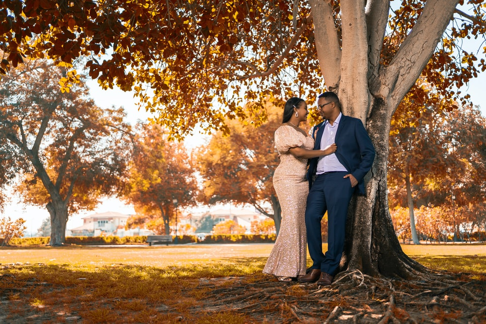 couple kissing under brown tree during daytime