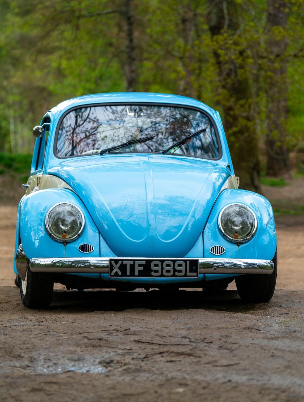 blue volkswagen beetle on road during daytime