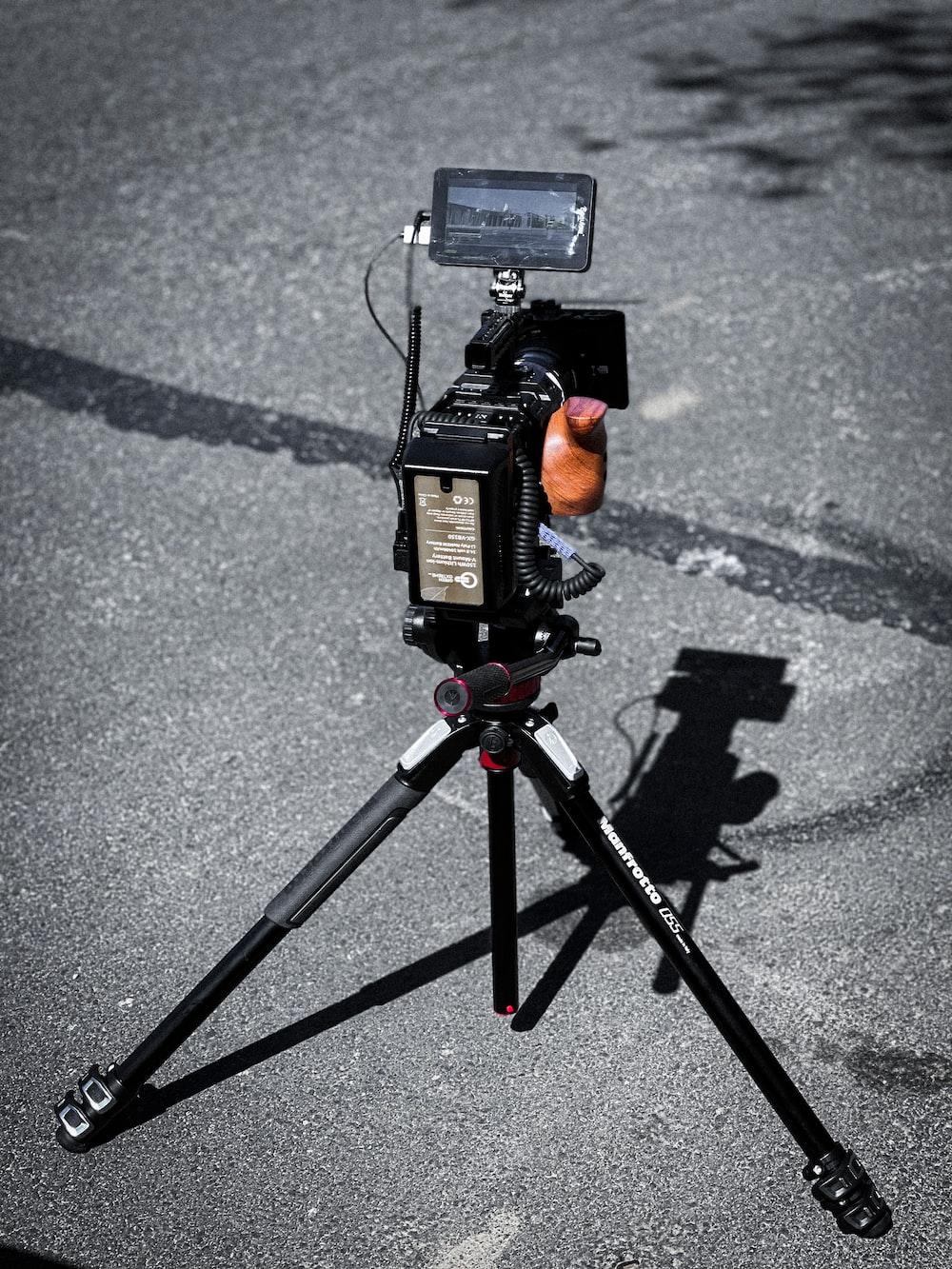 black dslr camera on tripod on road during daytime