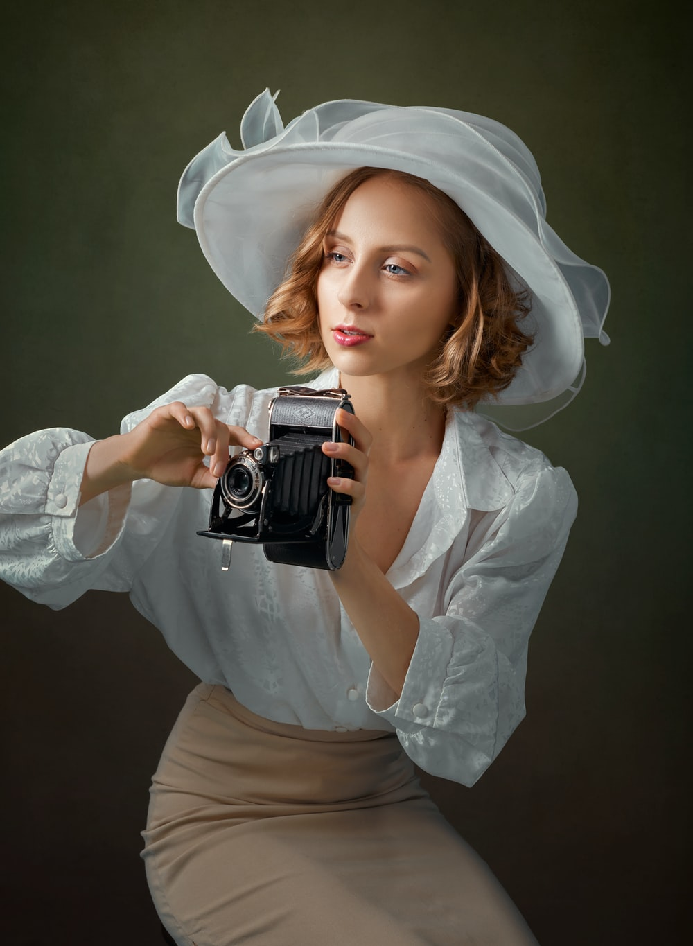 woman in white long sleeve shirt holding black and silver camera