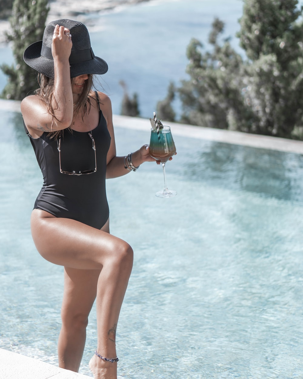 woman in black one piece swimsuit holding blue and green plastic cup
