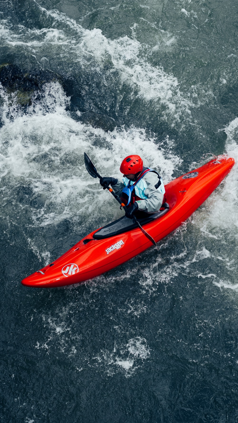 man in red and black wet suit riding orange kayak on water