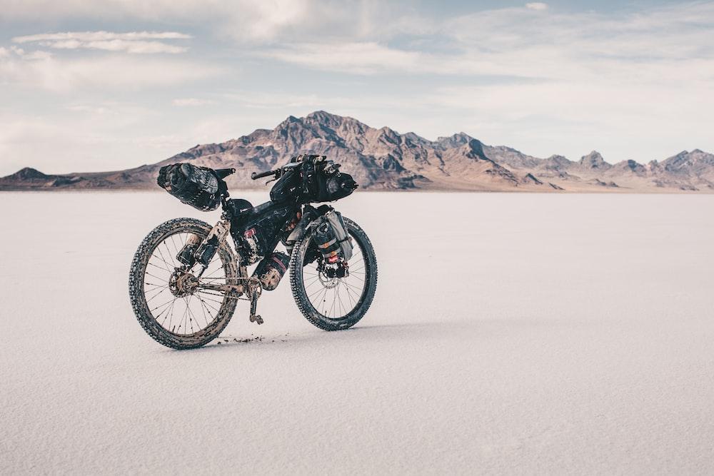 black mountain bike on white sand near body of water during daytime