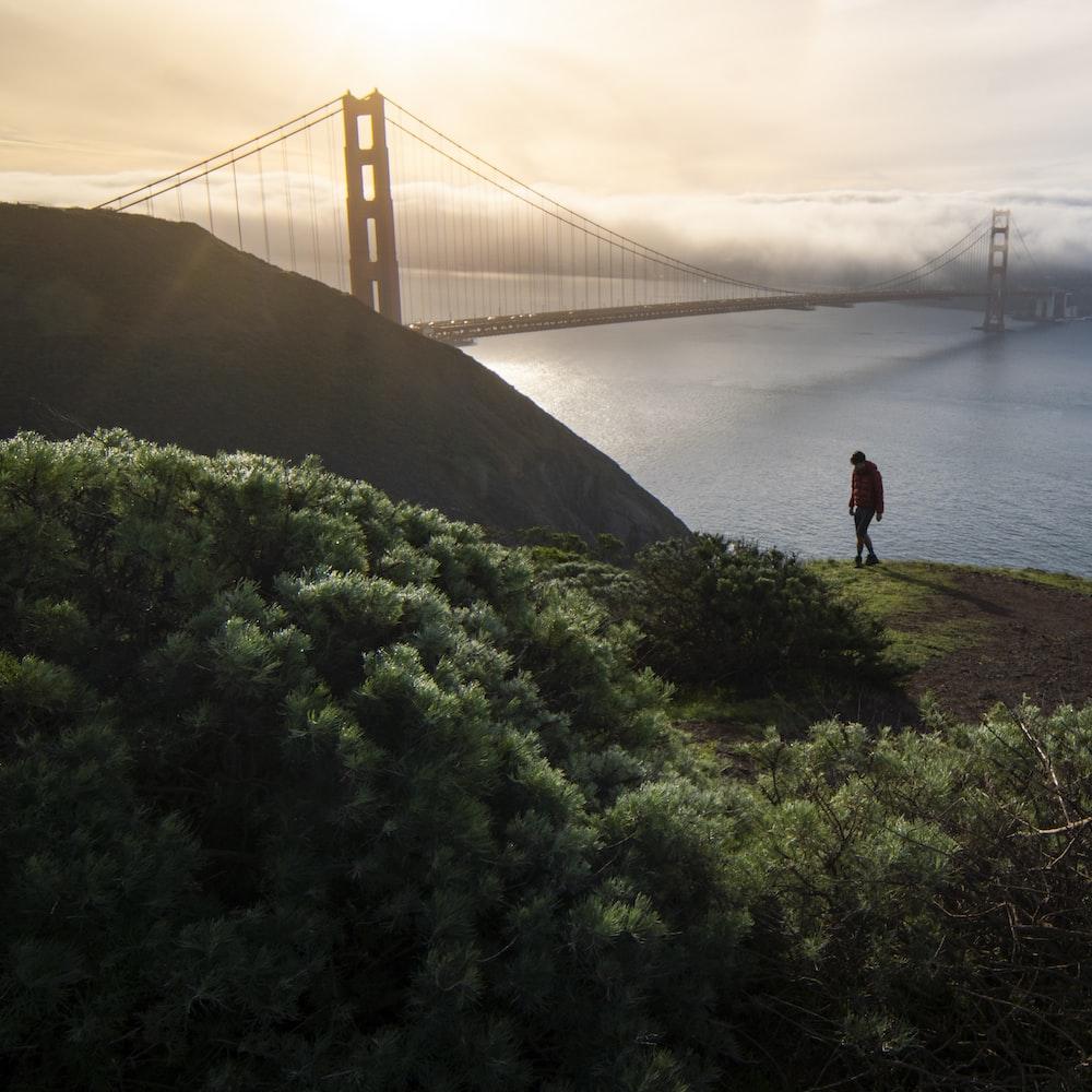 person standing on green grass near golden gate bridge during daytime