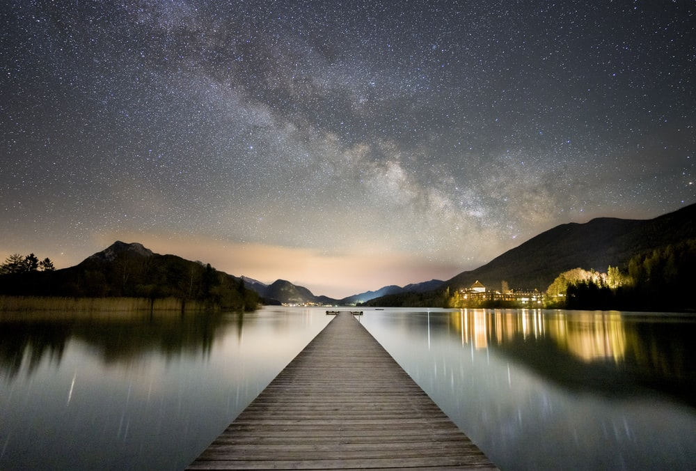 brown wooden dock on lake during night time