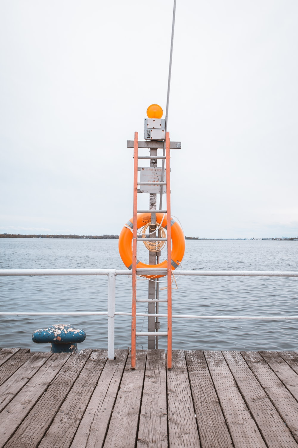 orange and white lifeguard tower near body of water during daytime