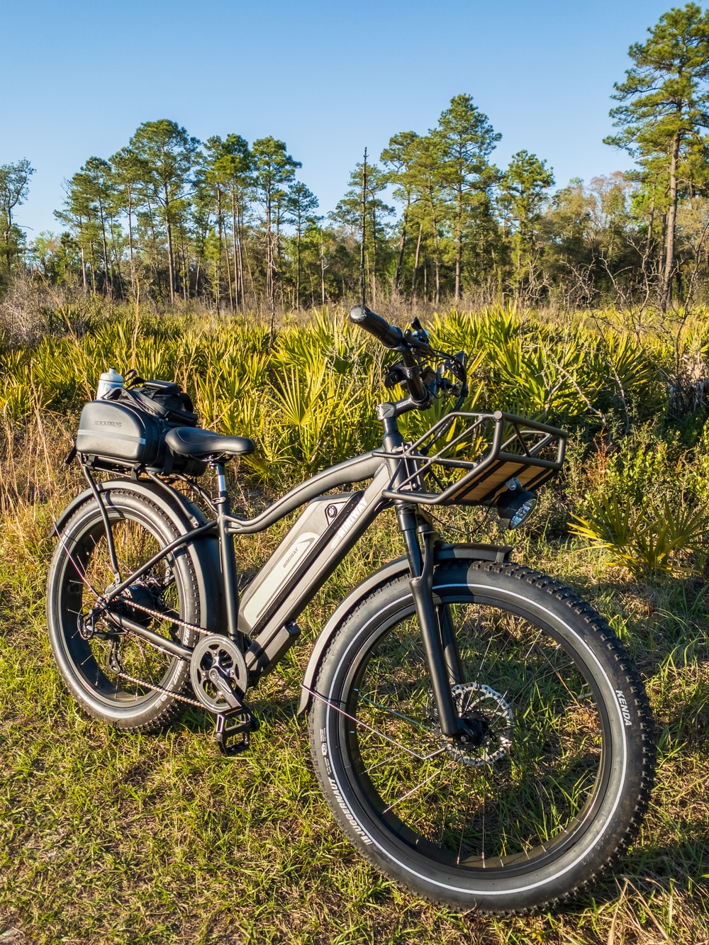black and white mountain bike on green grass field during daytime
