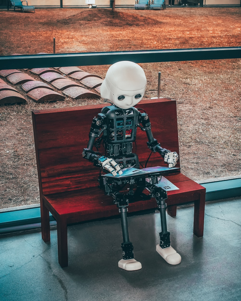 black and white robot toy on red wooden table