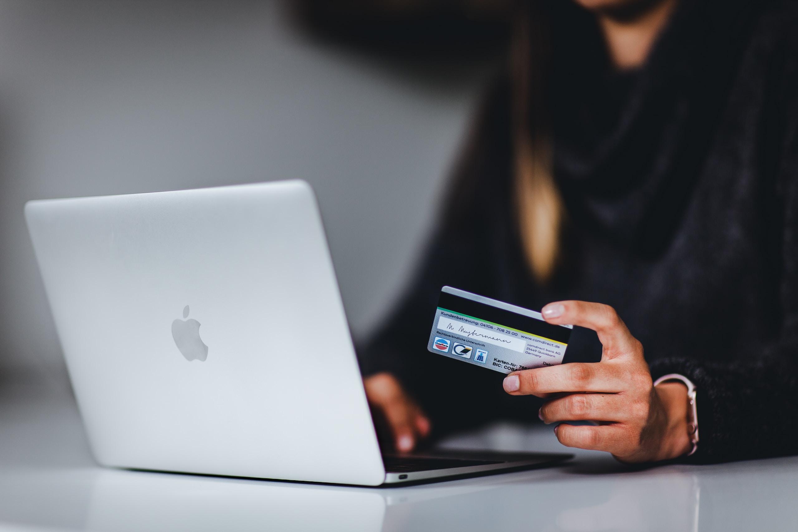 Frau mit schwarzem Smartphone in der Nähe von silbernem MacBook