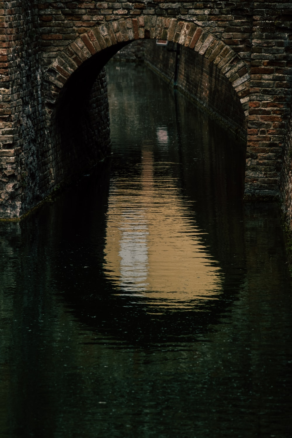 reflection of gray concrete bridge on water during daytime