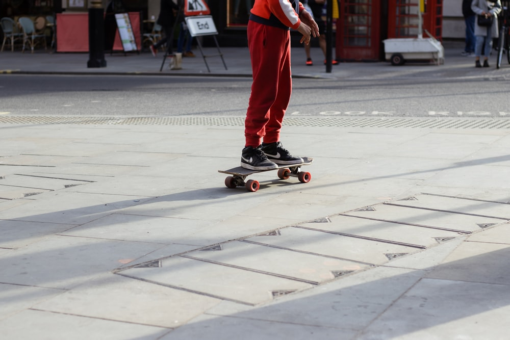 man in red pants and black shoes riding skateboard on gray concrete road during daytime