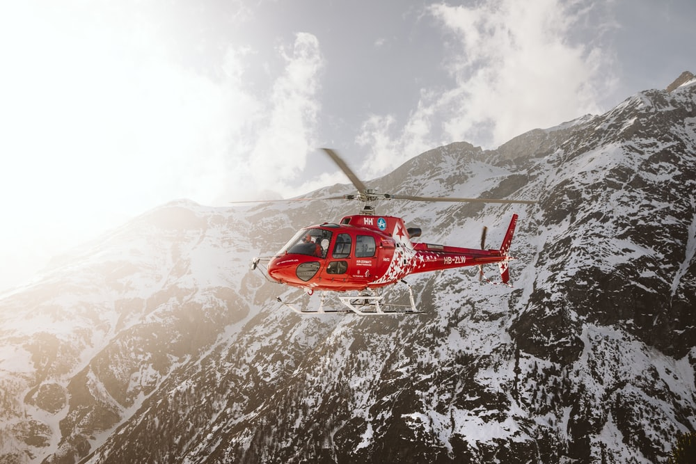 red and white helicopter flying over snow covered mountain during daytime