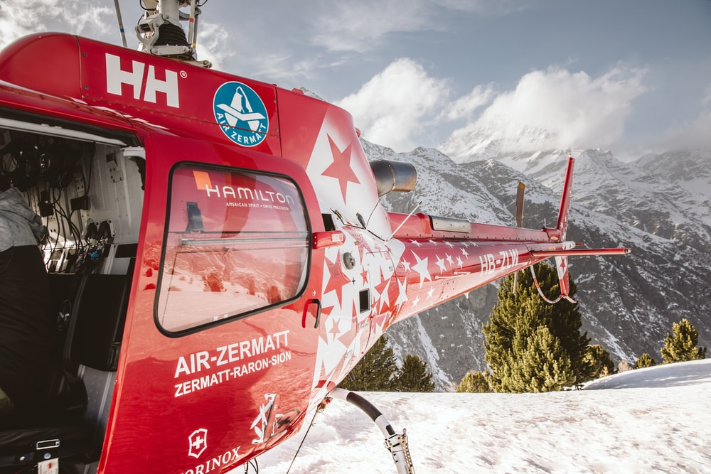 red and white helicopter flying over snow covered ground during daytime