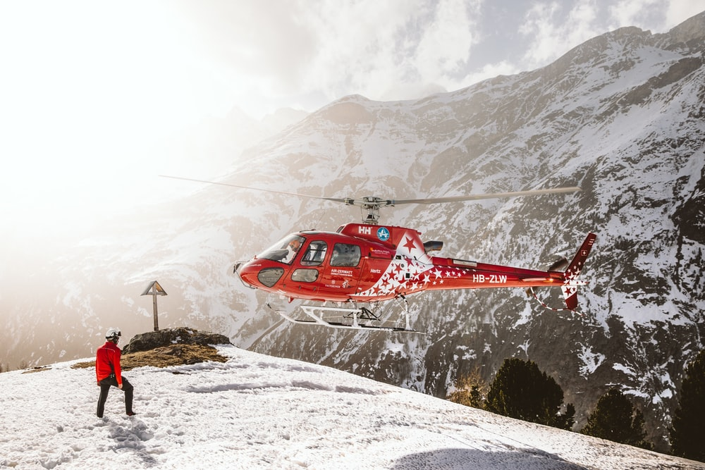 red helicopter flying over snow covered mountain during daytime