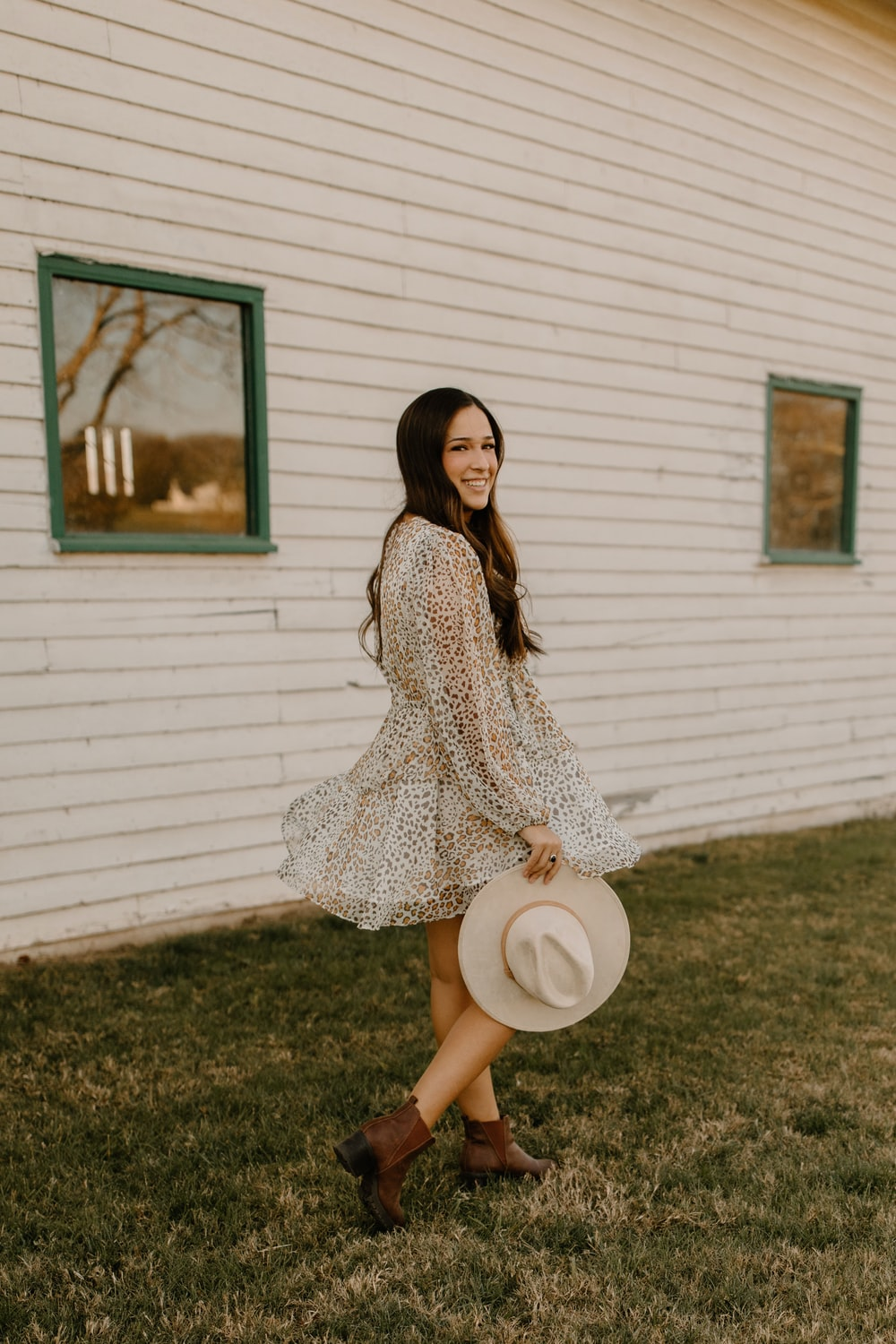 woman in white and black long sleeve dress holding white hat