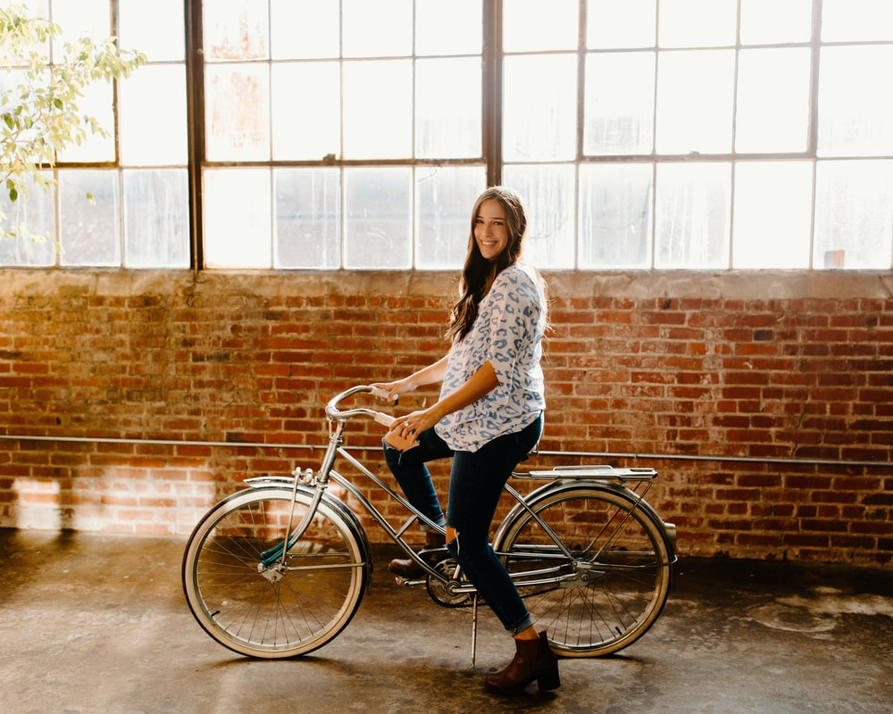 woman in white and black floral long sleeve shirt riding on bicycle