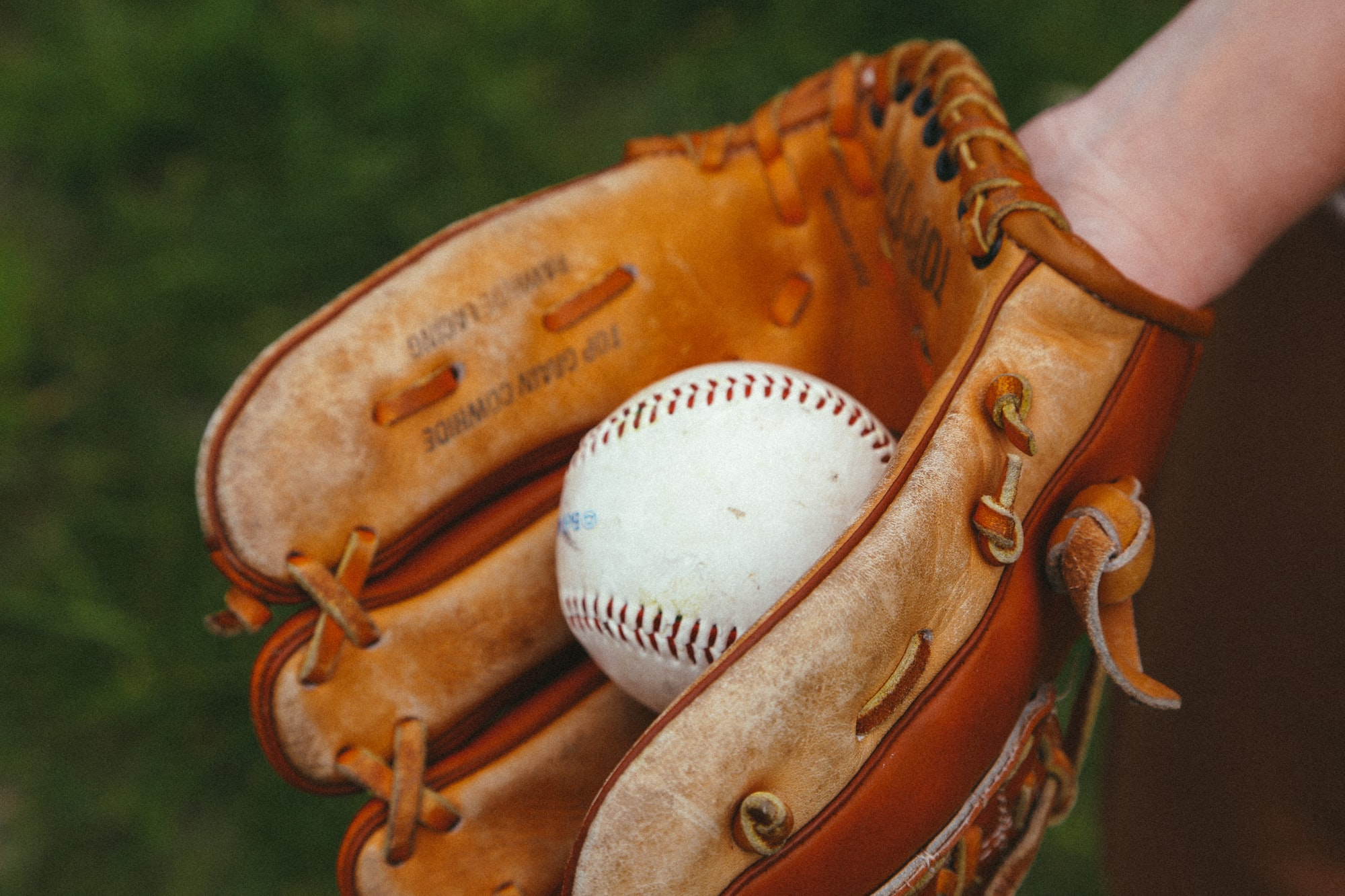 Baseball in hand and glove. Throw. Baseball equipment. Sport. The game. Advertising. Place for an inscription. The close plan.