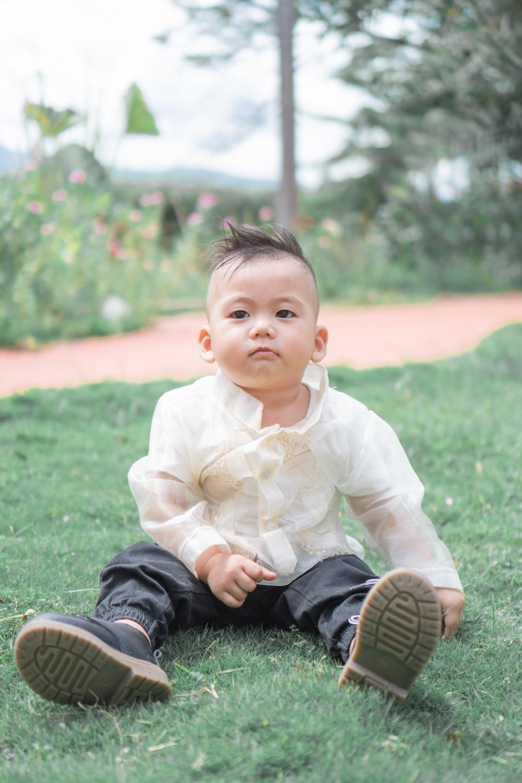 boy in white dress shirt sitting on green grass during daytime