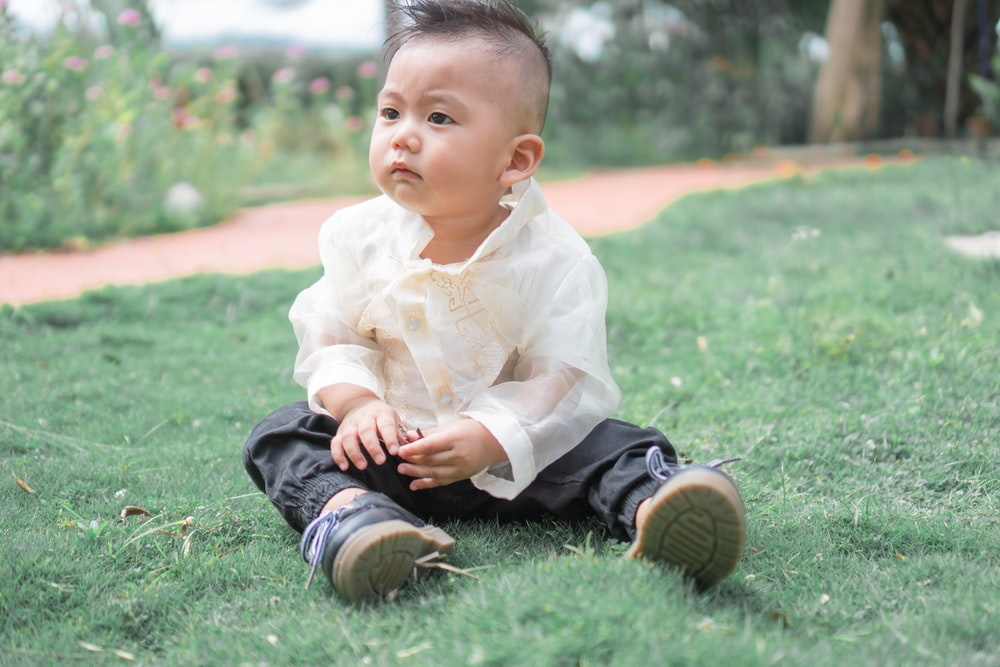 baby in white dress shirt and black pants sitting on green grass during daytime
