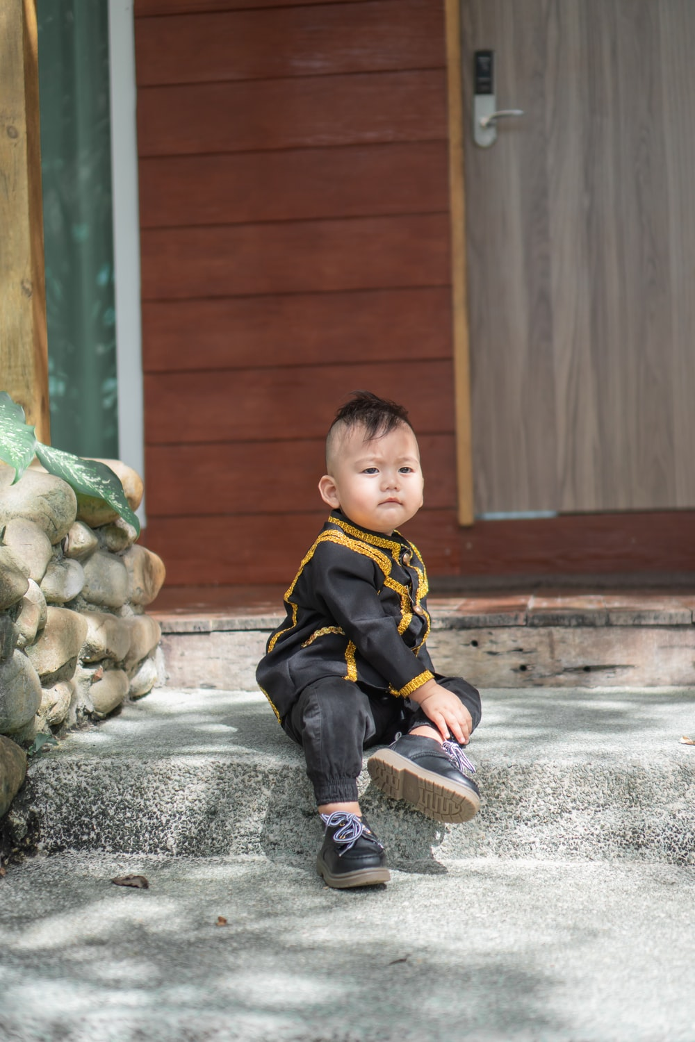 boy in black and yellow jacket sitting on gray concrete floor