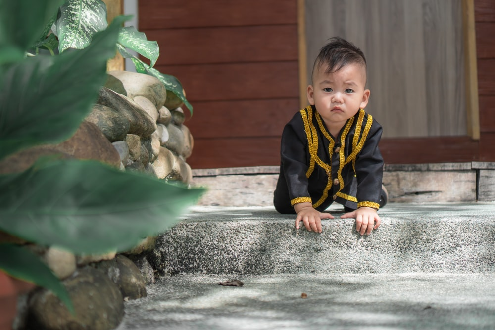 boy in black and yellow zip up jacket sitting on gray concrete fountain during daytime