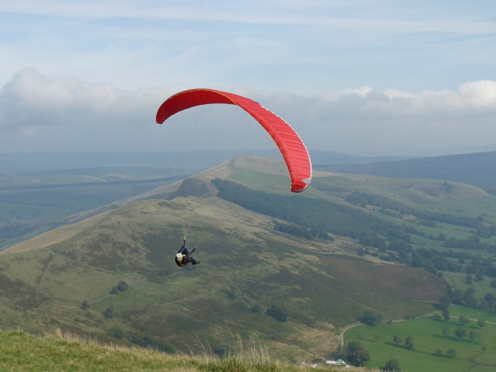 person in black jacket riding red parachute over green grass field during daytime