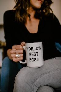 woman in black v neck shirt holding white ceramic mug