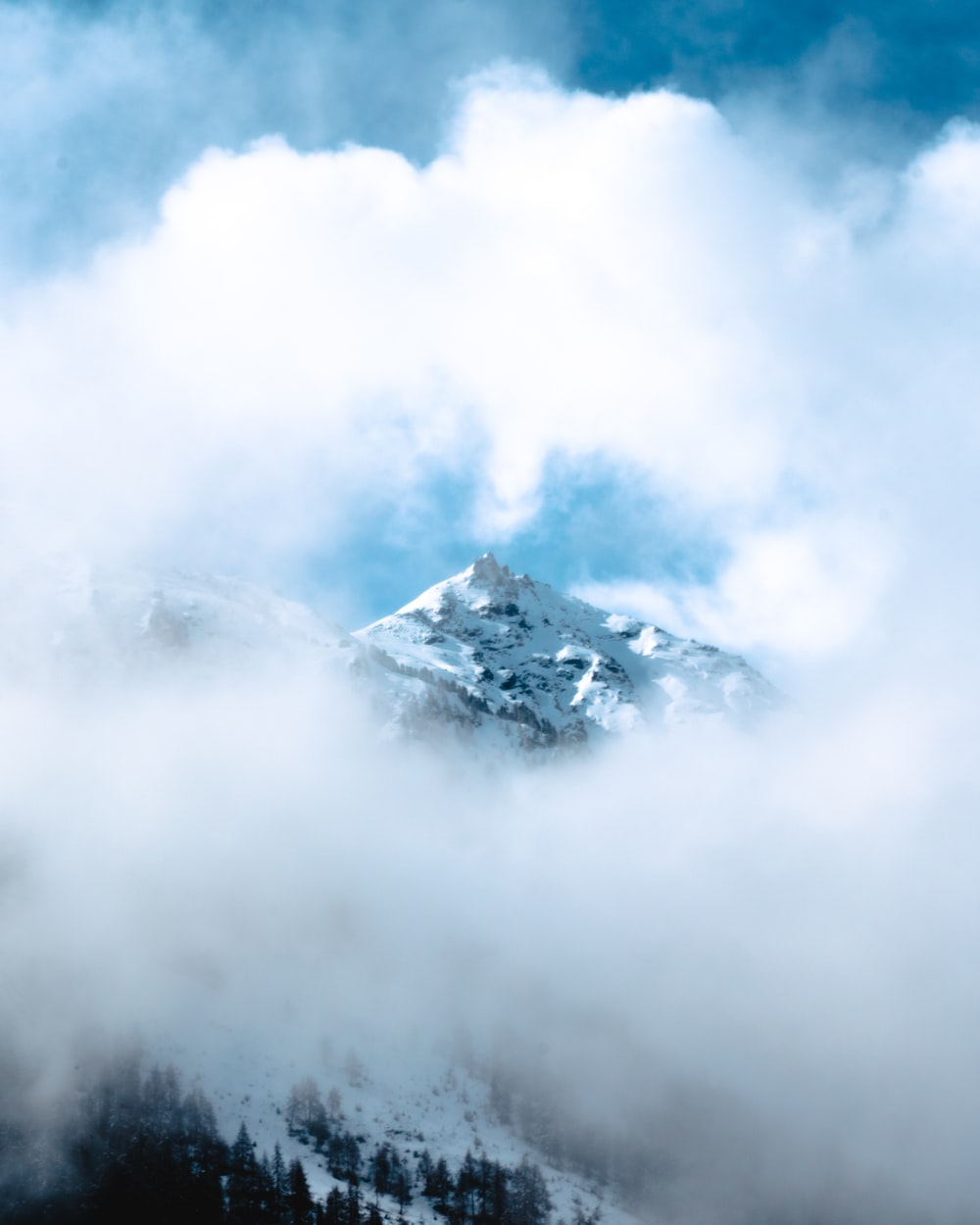 snow covered mountain under white clouds during daytime