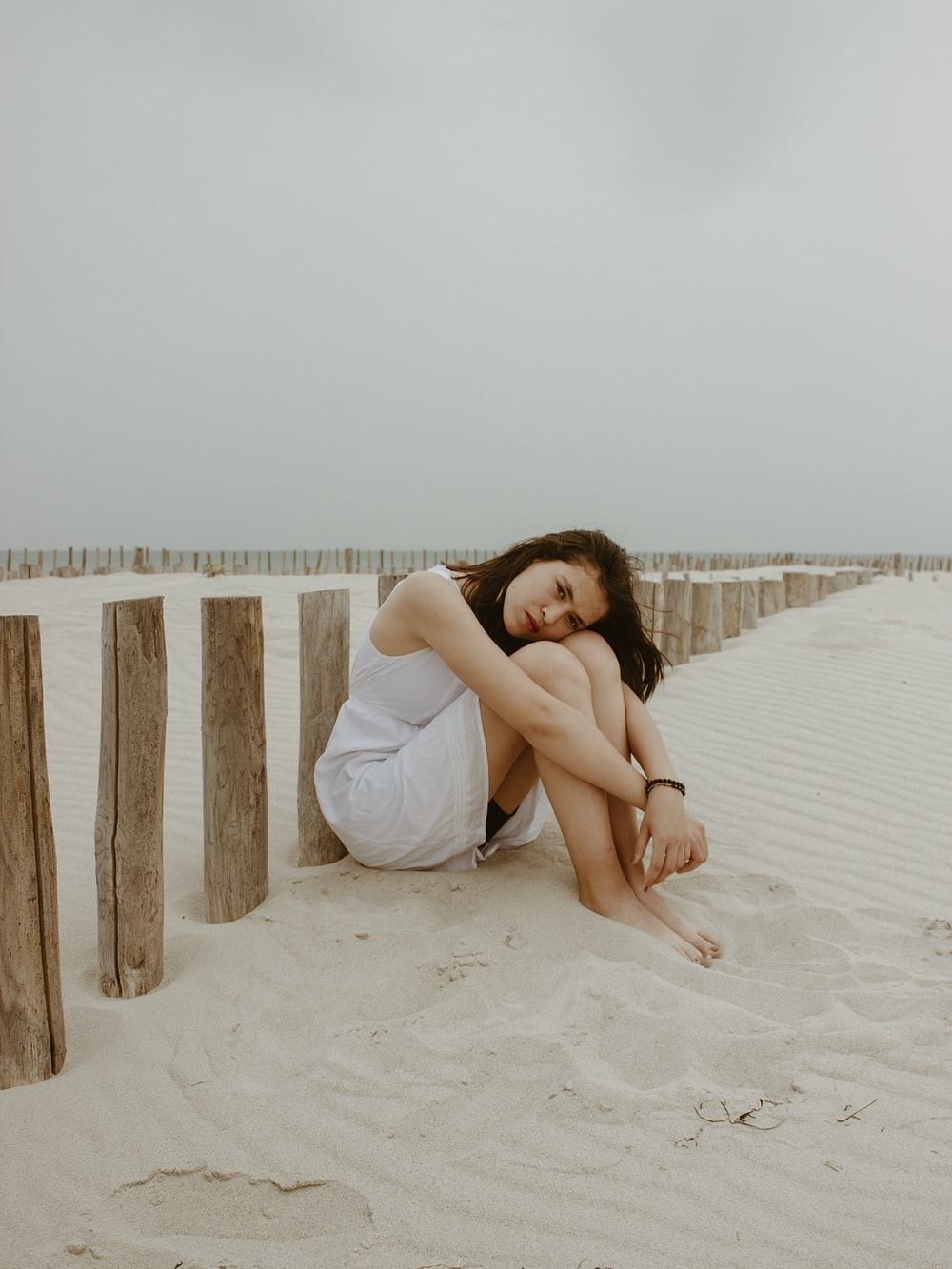 woman in white dress sitting on white sand during daytime