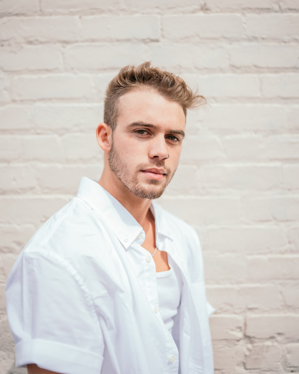 man in white button up shirt standing beside white wall