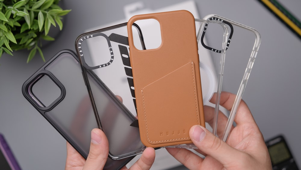 person holding orange leather smartphone case